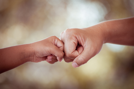 mother and kid daughter are fist bumping in vintage color tone