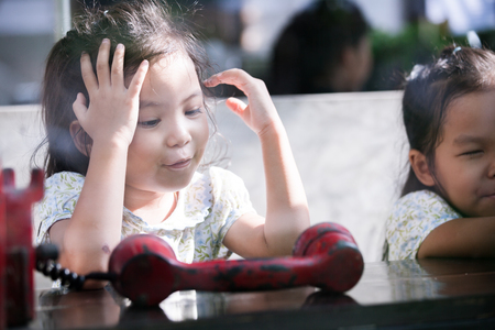Happy asian little girl playing and talking phone in cafe in vintage color tone