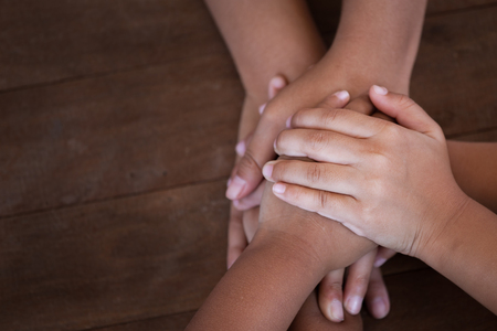 Family and children holding hands together on wooden background
