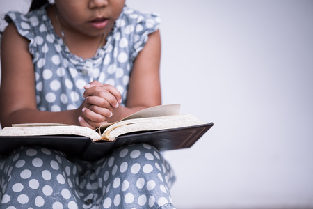 Little girl hands folded in prayer on a Holy Bible on white background  for faith concept in vintage color tone Stock fotó