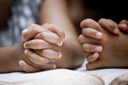 Two Little girl hands folded in prayer on a Holy Bible together  for faith concept in vintage color tone