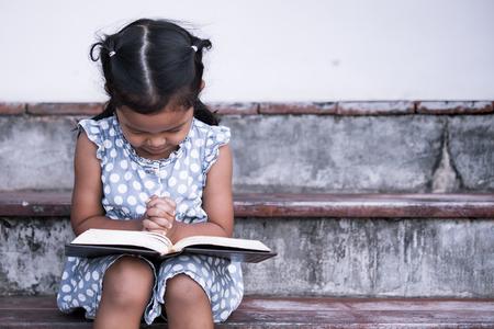 かわいいアジアの女の子彼女の目を閉じ、ヴィンテージ色のトーンの信仰概念聖書の祈りで彼女の手を折られました。