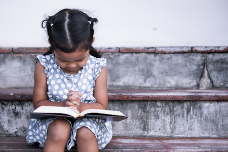 Cute asian little girl closed her eyes and  folded her hand in prayer on a Holy Bible for faith concept in vintage color tone Stock Photo