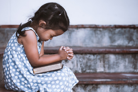 Cute asian little girl closed her eyes and  folded her hand in prayer on a Holy Bible for faith concept in vintage color tone 免版税图像