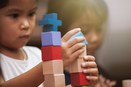 Focus on childs hand  playing with colorful wooden blocks in vintage color tone