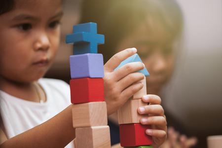 Konzentrieren Sie sich auf die Hand des Kindes, die mit bunten Holzklötzen im Weinlesefarbton spielt Standard-Bild - 78416079