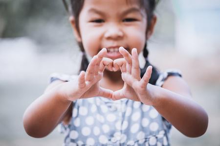 빈티지 색조 손으로 심장 모양을 만드는 아시아 어린 소녀 스톡 콘텐츠