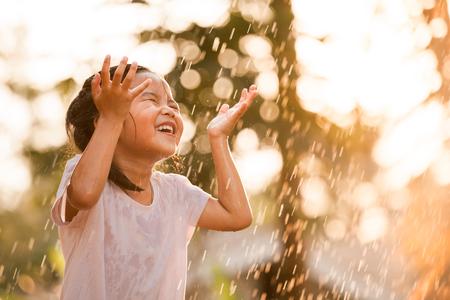 Heureuse petite fille asiatique s'amuser à jouer avec la pluie dans le ton de couleur vintage