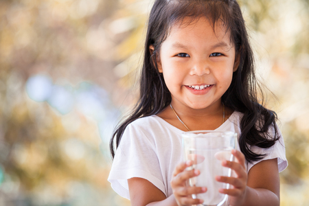 Cute asian little girl holding glass of fresh water in vintage color tone Reklamní fotografie