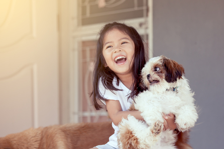 Cute asian little girl with her Shih Tzu dog in vintage color tone Stock Photo