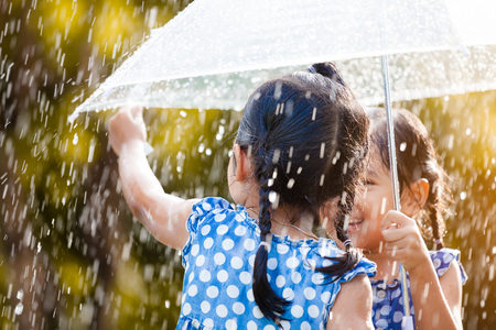 Back view of two asian little girls with umbrella having fun to play with the rain together in vintage color tone