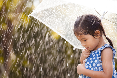 Lonely asian little girl with umbrella in rain