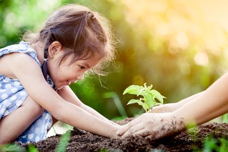 Asijská malá holčička a rodiče vysazují mladý strom na černé půdě společně jako zachránit světový koncept ve vinobraní barevný tón