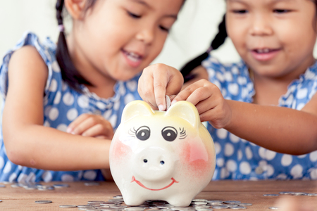 fingers put together: Two asian little girls having fun to put coin into Piggy Bank together,kid saving money for the future concept
