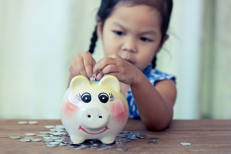 Child asian little girl putting coin into Piggy Bank in vintage color tone,kid saving money for the future concept