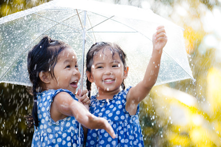 Two happy asian little girls with umbrella having fun to play with the rain together in vintage color tone Archivio Fotografico