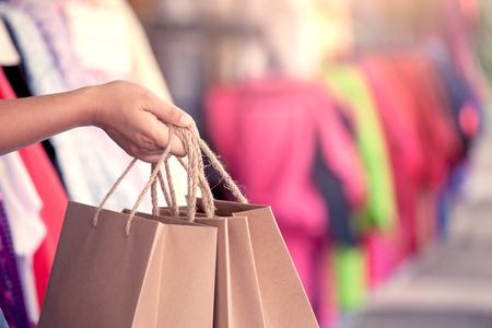 De holding van de vrouwenhand het winkelen doet op de straat in het winkelcomplex in uitstekende kleurentoon in zakken Stockfoto