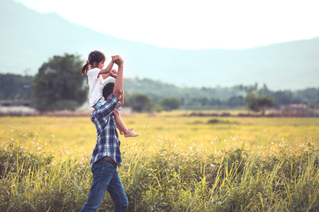 Father and daughter having fun to play together in the cornfield and child riding on fathers shoulders in vintage color tone
