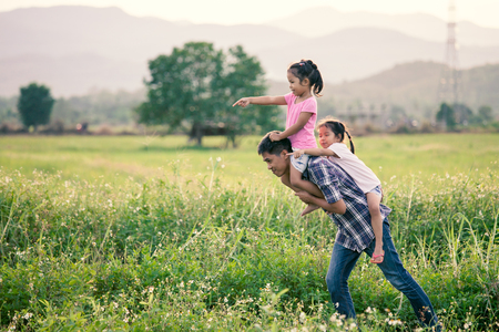 Father and daughter having fun and playing together in the cornfield and child riding on fathers back and shoulder in vintage color tone Reklamní fotografie