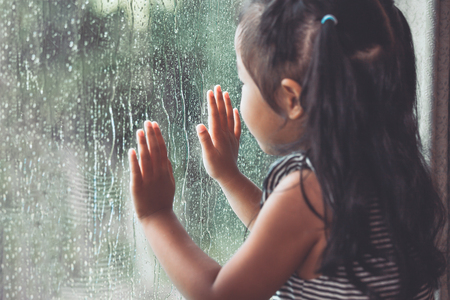 Sad asian little girl looking outside through the window in the rainy day in vintage color tone Foto de archivo