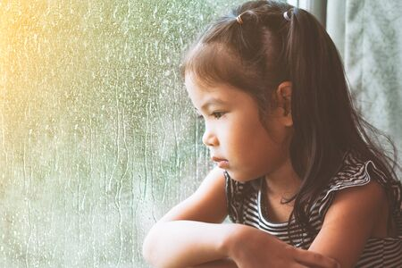 sobbing: Sad asian little girl looking outside through the window in the rainy day in vintage color tone Stock Photo