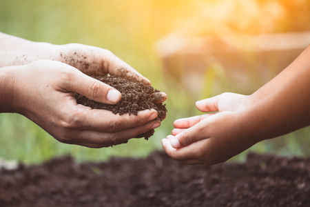 Mothers hand giving soil to a child for planting together in vintage color tone