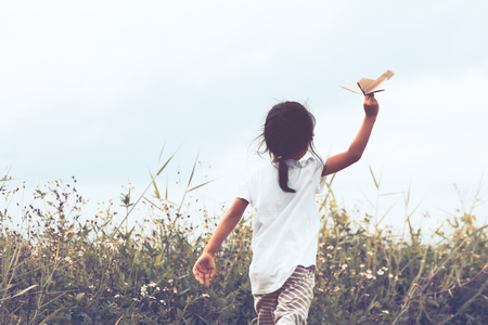 Back view of asian child playing toy paper airplane in the meadow in vintage color tone