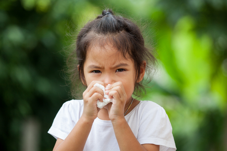 Sick little asian girl wiping or cleaning nose with tissue on her hand Standard-Bild