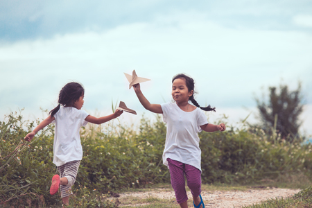 two tone: Two asian children playing with toy paper airplane in the meadow together in vintage color tone Stock Photo