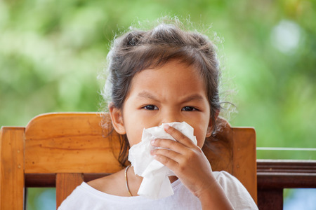 Sick little asian girl wiping or cleaning nose with tissue on her hand Stock Photo