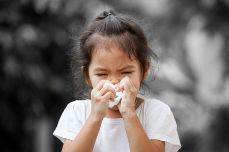 Sick little asian girl wiping or cleaning nose with tissue on her hand on black and white background Standard-Bild