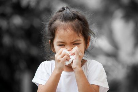 Ziek weinig Aziatische meisje afvegende of schoonmakende neus met weefsel op haar hand op zwart-witte achtergrond Stockfoto