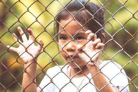 metal grate: Child little girl hand holding steel mesh in vintage color tone