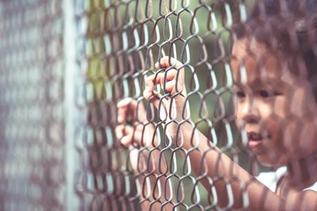 imprisoned: Child little girl hand holding steel mesh in vintage color tone
