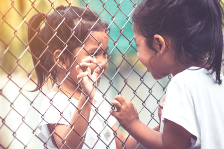 Two asian kids talking to each other and hand holding steel mesh in vintage color tone
