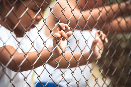 imprisoned: Child little girl hand holding steel mesh with her friend in vintage color tone