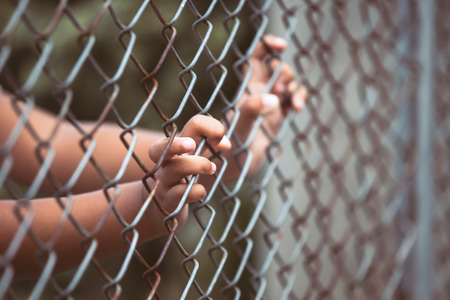 jail: Child little girl hand holding steel mesh in vintage color tone