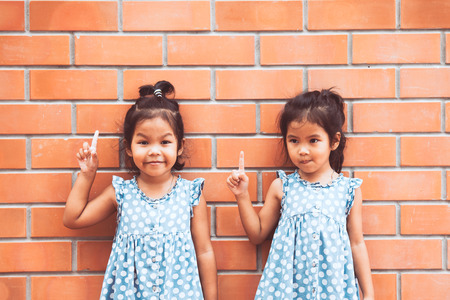two tone: Portrait of two asian kid girls pointing up on brick wall background in vintage color tone