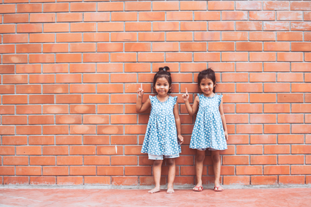 Portrait of two asian kid girls pointing up on brick wall background in vintage color tone