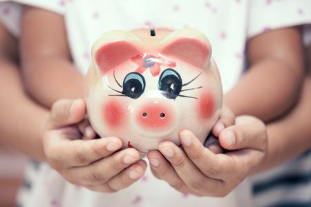 Sparschwein in Kinderkinder- und -mutterhänden im Weinlesefarbton. Familie, Sparen, Anlagekonzept Standard-Bild - 81286240