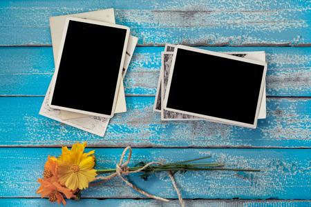 Leeg fotokaderalbum met bloem op oude blauwe houten achtergrond Stockfoto