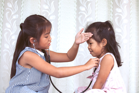 의사와 환자 빈티지 색상 톤에서 함께 연주 두 귀여운 아시아 아이 소녀 스톡 콘텐츠