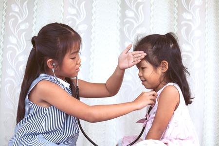 Dos niñas lindas niño asiático jugando médico y paciente juntos en tono de color de la vendimia Foto de archivo - 81544243