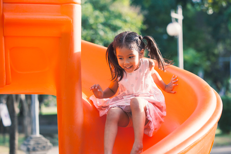 Cute asian child girl having fun to play slider in the playground in summer time