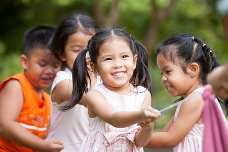 Asian children having fun to play tug-of-war with rope together in the park in vintage color tone