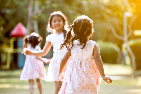 Back view of asian child girl running to her friend and play together in the park in vintage color tone