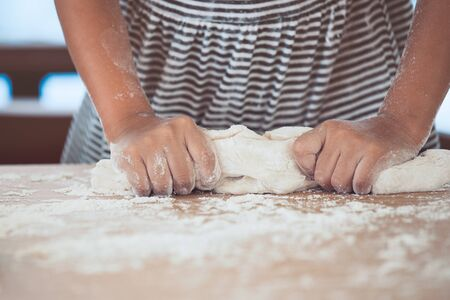 easter cookie: Little child girl hands kneading dough prepare for baking cookies in vintage color tone