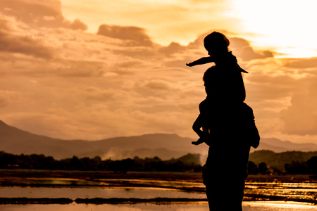 Silhouette asian little girl riding on fathers shoulder and playing together with sky and cloudy in the cornfield at sunset