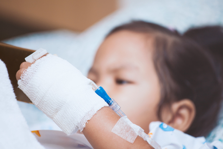 Child's patient hand with saline intravenous (iv) drip in the hospital