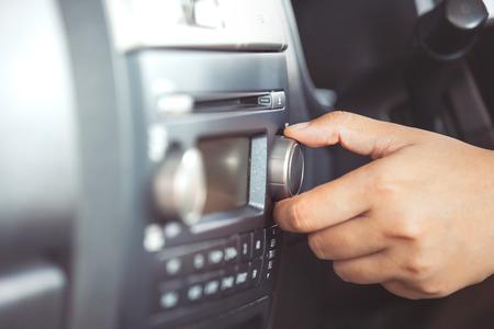 Vrouwenhand die het correcte volume van autoradio aanpassen terwijl het drijven van een auto in uitstekende kleurentoon